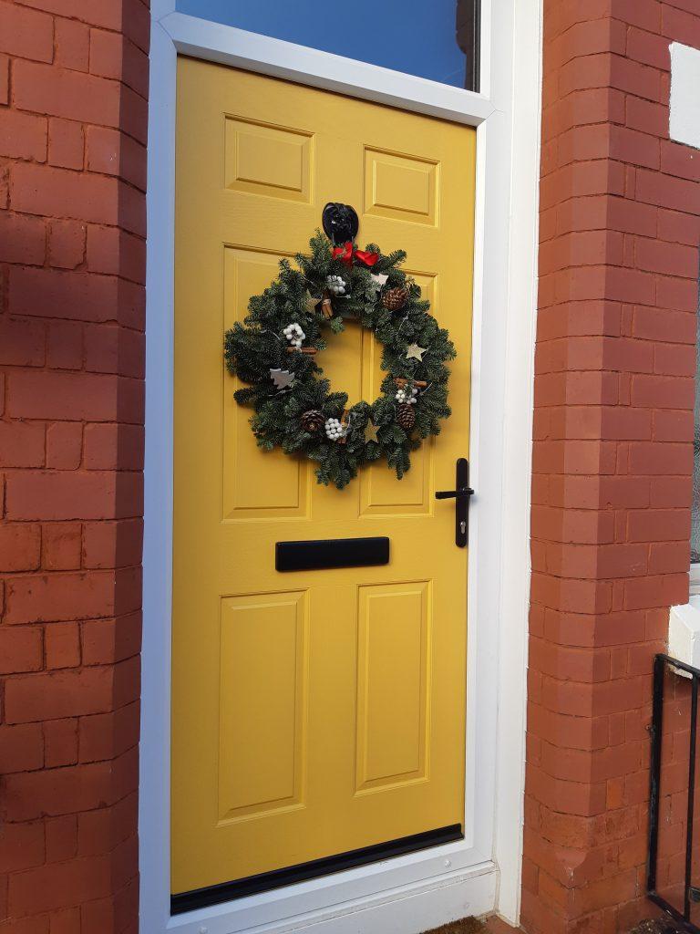 Yellow composite door with christmas wreath