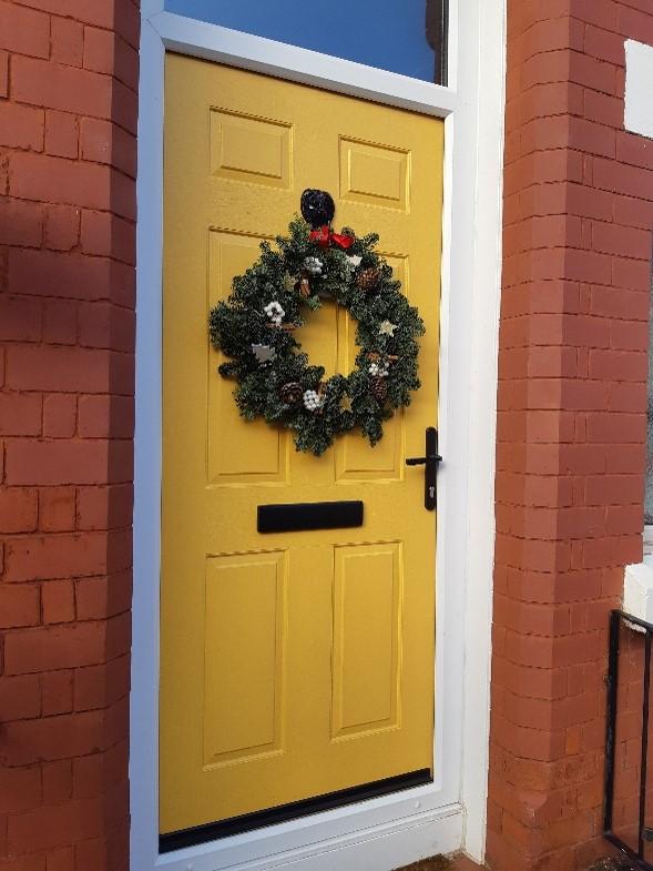 Block yellow front door with xmas wreath