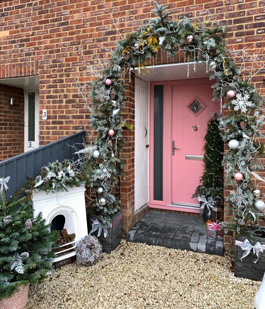 Pink front door with sidelight adorned with christmas decorations